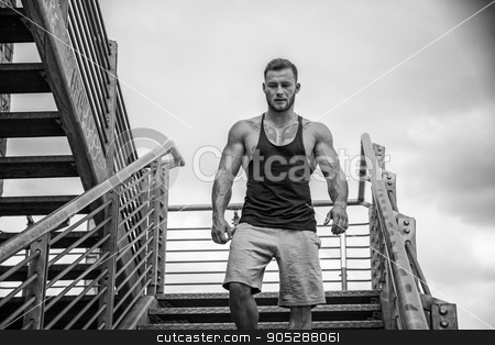 Handsome muscular man standing outdoor in city stock photo, Handsome muscular man standing in city setting looking away to a side, walking down metal stairs by Stefano Cavoretto