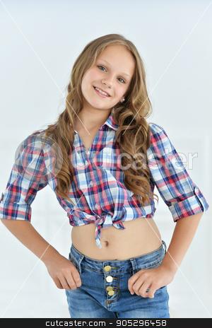 cute little girl posing  stock photo, cute little girl posing in shirt and jeans   in studio by Ruslan Huzau