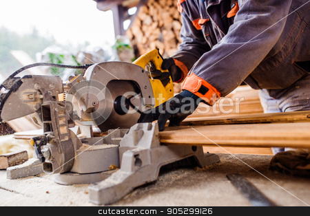Carpenter working. Man cutting plank by circular saw stock photo, Hands of unrecognizable carpenter working. Man using circular saw to cut planks of wood for home construction by HalfPoint