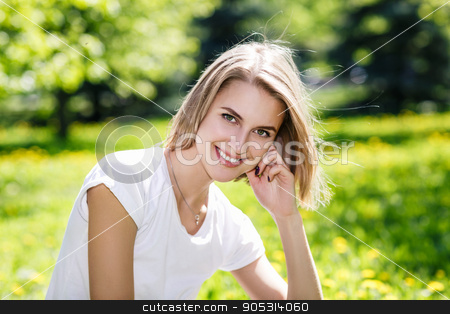 Beautiful young woman in the summer outdoors stock photo, Close portrait of beautiful young woman on green grass in the summer outdoors by Dmitrii Kotin