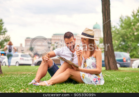 Young tourist couple in the grass stock photo, A beautiful young couple are siting in the grass having an ice-cream with the Castle in background in Budapest, Hungary.  by Michael Osterrieder