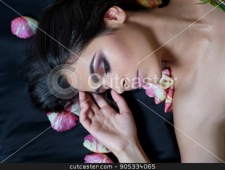 Portrait of a beautiful young woman laying on sparse rose petals stock photo, Portrait of a beautiful young woman laying on sparse rose petals by timonko