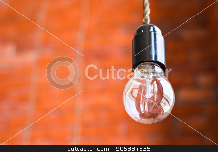 Incandescent lamp on a brick wall background stock photo, Incandescent lamp on a orange brick wall background by Satura86