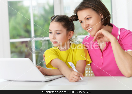 mother  and daughter with laptop stock photo, portrait of mother  and daughter with laptop at home by Ruslan Huzau