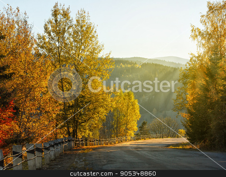 Rural landscape with old road in autumn forest stock photo, Rural landscape with old road in autumn forest against the backdrop the mountains by serkucher