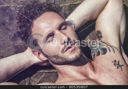 Handsome muscular man on the beach laying on rocks stock photo, Handsome muscular shirtless man on the beach lying on rocks, with eyes closed by Stefano Cavoretto