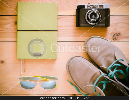 top view set with old camera, boots, sunglasses stock photo, Set of travel and resort stuff. Old 35 mm camera, note book, sunglasses and desert boots on wooden table. Top view, flat lay. Toned image by Fascinadora