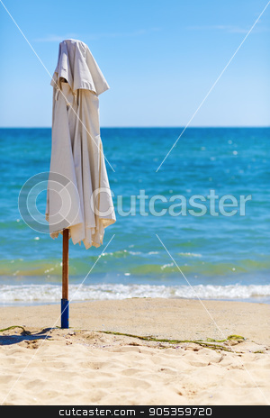 Folded parasol stock photo, Folded parasol on the beach against the bright blue sky, sea and sand. by Veresovich