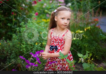 Cute happy girl in a green blooming garden stock photo, Cute happy girl in a blooming garden by HDesert