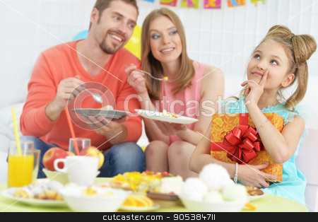 parents and daughter  with cake stock photo, Happy  parents and daughter  with cake at birthday party by Ruslan Huzau