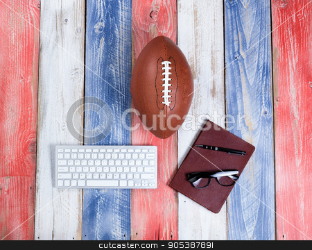 Analyzing American football for the season on rustic boards pain stock photo, Overhead view of computer keyboard, reading glasses, notepad, pen and American football on red, white and blue rustic wooden boards. Concept of draft day and future plays for the season.  by tab62
