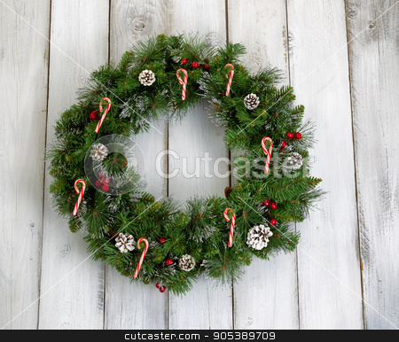 Christmas wreath with decorations on rustic white wooden boards stock photo, Christmas wreath decorated with pine cones, candy canes, and red berries on rustic white wooden boards.  by tab62
