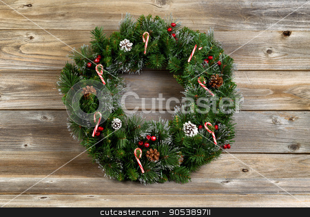 Christmas wreath with decorations on rustic wooden boards stock photo, Christmas wreath decorated with pine cones, candy canes, and red berries on rustic wooden boards.  by tab62