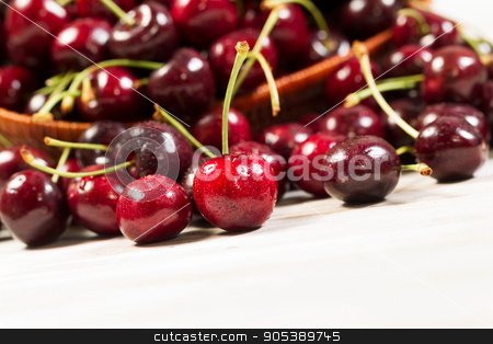 Closeup of fresh ripe black cherries  stock photo, Closeup horizontal view of black cherries, focus on front upright cherry, spilled out of basket onto white boards by tab62