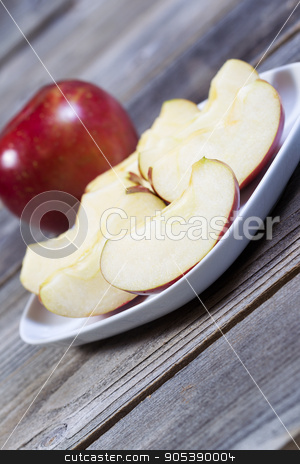 Apple Slices  stock photo, Angled vertical photo of fresh apple slices, on white plate, with whole apple and rustic wood in background   by tab62