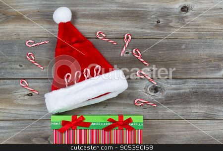 Holiday Decorations on Rustic Wood  stock photo, Top view close up of candy canes, gift and Santa hat placed on rustic wood  by tab62