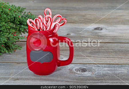 Holiday Mug filled with treats  stock photo, Close up of a red mug filled with holiday candy canes with partial Christmas tree on rustic wood  by tab62