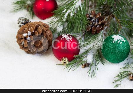 Christmas Ornaments on Snow with Pine Tree Branch  stock photo, Horizontal view of Christmas ornaments, resting in white snow, with evergreen tree branch in background  by tab62