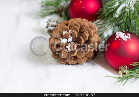 Closeup of a Pine Cone on Snow with Pine Tree Branch and Ornamen stock photo, Closeup horizontal view of large pine cone, resting in white snow, with Christmas ornaments and evergreen tree branch in background  by tab62