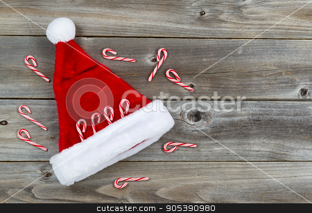 Santa Hat and Candy Canes on Rustic Wood  stock photo, Top view close up of candy canes and Santa hat placed on rustic wood  by tab62
