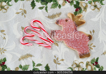 Holiday Treats  stock photo, Top view close up of seasonal candy canes and cookie reindeer placed on holiday table cloth   by tab62