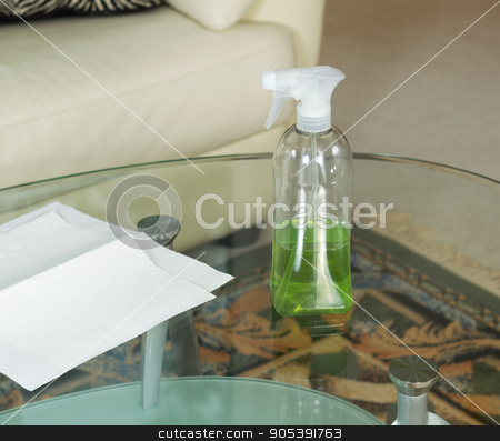 Cleaning Solution Spray Bottle on Top of Dirty Glass Table  stock photo, Photo of cleaning solution, in spray bottle, on dirty glass table with paper towels and sofa in background  by tab62