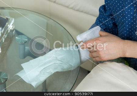 Cleaning underneath Glass End Table  stock photo, Horizontal photo female hands wiping underneath glass round end table with spraying cleaning solution bottle and paper towels in hand with sofa and partial lamp in background  by tab62