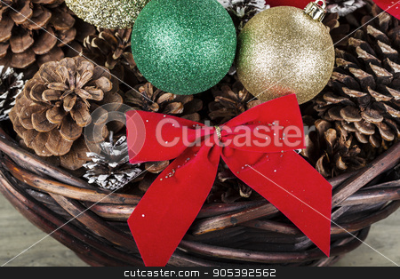 Holiday Basket  stock photo, Basket full of pine cones, ornaments and ribbons for the Christmas season  by tab62