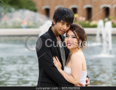 Young Adult Couple Closely Holding Each Other  stock photo, Closeup horizontal photo of young adult couple, looking forward, while holding each other with water fountain, flowers, trees and brick building in background  by tab62