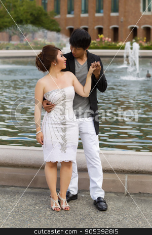 Young Adult Couple Holding Hands Near the Water Fountain  stock photo, Vertical photo of young adult man holding his lady hand with water fountain, flowers, trees and brick building in background  by tab62