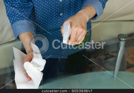 Spraying Cleaning Solutions onto Glass Table  stock photo, Horizontal photo female hands spraying cleaning solution, from spray bottle, onto dirty glass table with paper towels and sofa in background  by tab62