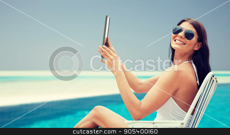 smiling woman with tablet pc sunbathing on beach stock photo, summer vacation, tourism, travel, holidays and people concept - smiling young woman with tablet pc computer sunbathing in lounge or folding chair over beach and swimming pool background by Syda Productions