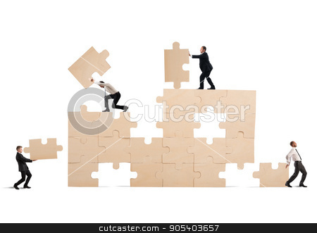 Build the business stock photo, Team of businessmen collaborate and cooperate to build a puzzle by Federico Caputo
