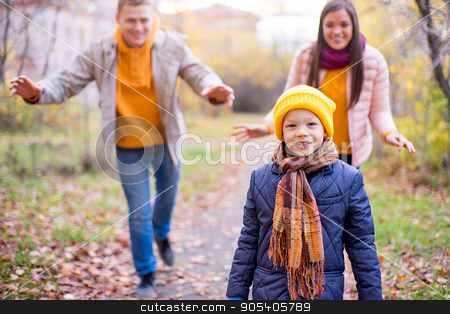 family playing catch-up stock photo, family playing catch-up on a footpath in autumn park by Elena Nichizhenova