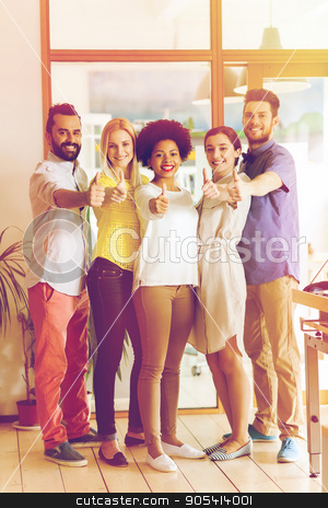happy creative team showing thumbs up in office stock photo, business, startup, people, gesture and teamwork concept - happy smiling international creative team showing thumbs up in office by Syda Productions