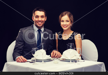 smiling couple holding hands at restaurant stock photo, restaurant, couple and holiday concept - smiling couple holding hands at restaurant by Syda Productions