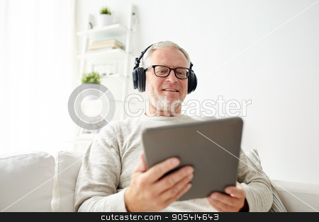 senior man with tablet pc and headphones at home stock photo, technology, people, lifestyle and distance learning concept - happy senior man with tablet pc computer and headphones listening to music at home by Syda Productions