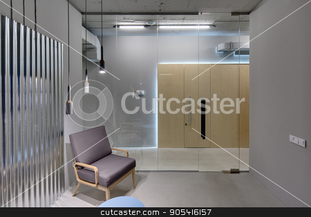 Office in loft style stock photo, Business interior in a loft style with gray walls. There is a room with a glass partition with door, an armchair, a small table and a metal panel on the wall. Opposite the room there are wooden doors by bezikus