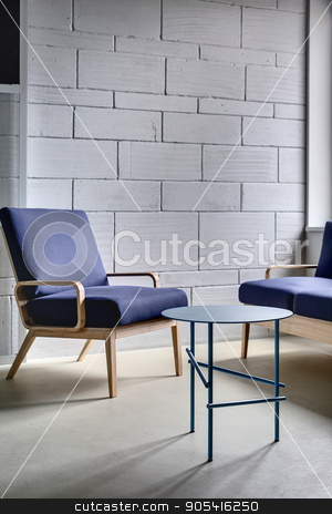 Interior in loft style stock photo, Blue armchair and a sofa with wooden legs on the background of the gray brick wall in the relax zone of the loft style office. Next to them there is a small blue round metal table. Vertical by bezikus