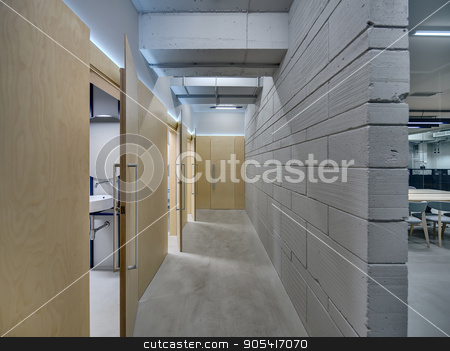 Corridor in loft style stock photo, Luminous corridor in the office in a loft style. There is a gray brick wall and wooden walls with several wooden doors. Three doors are open. Indoors. Horizontal by bezikus