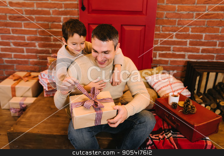 The father gives his son a gift for Christmas stock photo, Young parents give his son a Christmas present by Igor Kopakov