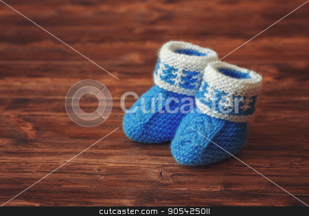 7264fc035480 Blue crochet baby booties on wooden background