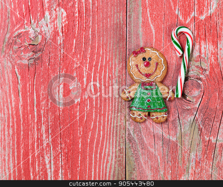 Gingerbread cookie and candy cane on rustic red wooden boards  stock photo, Christmas holiday cookie and candy cane on rustic red wood.     by tab62