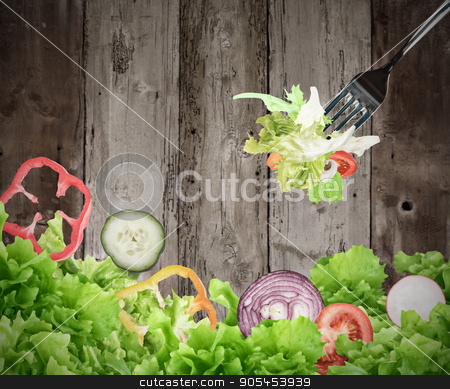 Background of mixed salad on wooden boards stock photo, Background of mixed salad eaten with a fork on wooden boards. Healthy food for wellness concept by Federico Caputo