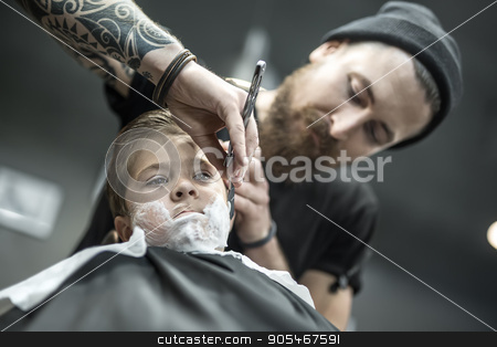 Funny shaving of little boy stock photo, Little kid with a shaving foam on the face in the barbershop. He wears a black salon cape. Bearded barber with a tattoo is shaving boy's face with the help of the straight razor. Low aperture photo by bezikus