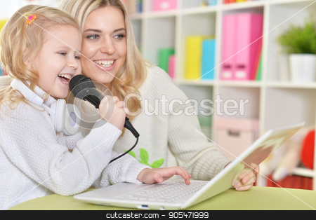 mother with little daughter singing  stock photo, Portrait of a mother with little daughter singing songs by Ruslan Huzau