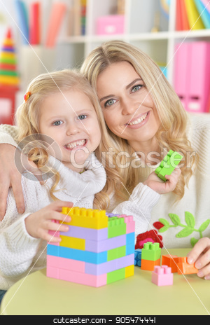 mother with little daughter  stock photo, mother with little daughter making figures with constructor by Ruslan Huzau