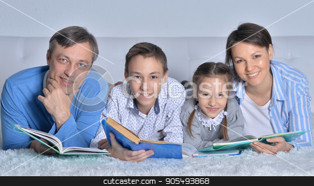 family reading books  stock photo, family reading books together on the floor by Ruslan Huzau