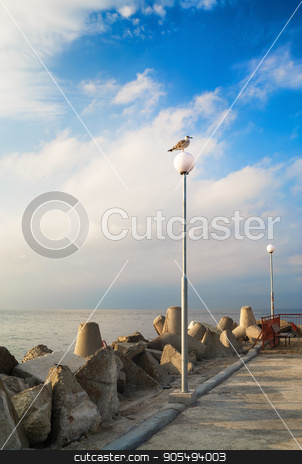 Pierce with lampposts stock photo, Pierce with lampposts. Breakwater with huge boulders on the coast of the Black Sea. Seagull on a post. Calm summer day. Vertical shot. by Veresovich