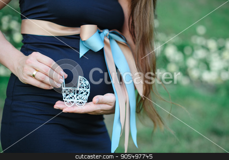 pregnant woman holding a toy stroller. concept idea stock photo, pregnant woman holding a toy stroller. concept idea by timonko
